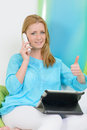 Beautiful woman at home with tablet shows thumb up