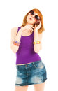 Beautiful woman in jeans skirt calling by phone and violet vest Royalty Free Stock Images