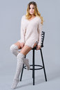 Beautiful woman in knitted knee socks sitting on a bar chair Royalty Free Stock Photo
