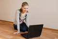 The beautiful woman with the laptop cheerful young sits on a floor Royalty Free Stock Photo