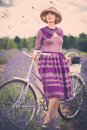 Beautiful woman in lavender field purple dress and hat with retro bicycle Stock Images