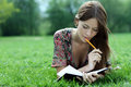 Beautiful woman lays on a grass in park with a diary in ha Royalty Free Stock Photo