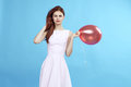 Beautiful woman on a light blue background holds a balloon Royalty Free Stock Photo