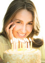 Beautiful woman with lit candles on cake portrait of young Stock Photography