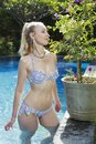 Beautiful woman with with a long blond  hair, a slim figure in a bikini swimwear in the pool with bright blue water in a tropical Royalty Free Stock Photo