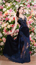 Beautiful woman in long blue lace dress on flower background. Fashion Royalty Free Stock Photo