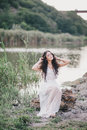 Beautiful woman with long curly hair dressed in boho style dress posing near lake young Stock Images