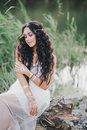 Beautiful woman with long curly hair dressed in boho style dress posing near lake young Royalty Free Stock Photos