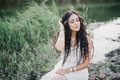 Beautiful woman with long curly hair dressed in boho style dress posing near lake Royalty Free Stock Photo