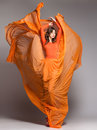 Beautiful woman in long orange dress posing dramatic