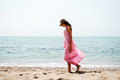 Beautiful woman with long pink dress and sun hat on a tropical b Royalty Free Stock Photo