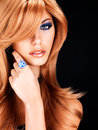 Beautiful woman with long red hairs with blue makeup portrait of a and fashion eye ring on finger on black background Stock Photo