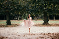 Beautiful woman in long rose evening dress walking path in park. Royalty Free Stock Photo