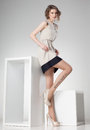 Beautiful woman with long legs dressed elegant posing in the studio - full body Royalty Free Stock Photo