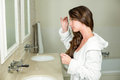 Beautiful woman looking in bathroom mirror Royalty Free Stock Photo