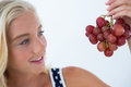 Beautiful woman looking at bunch of red grapes Royalty Free Stock Photo