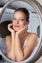 Beautiful woman looking through washing machine closeup of young sideways door Royalty Free Stock Photos