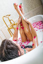 Beautiful woman lying in bath with flowers Royalty Free Stock Photo