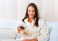 Beautiful woman lying in bed enjoying and watching television happy Stock Photos