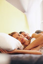 Beautiful woman lying on bed with her husband sleeping young couple together young women and looking at camera Royalty Free Stock Image