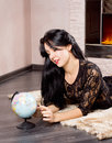 Beautiful woman lying floor front fire playing globe sweet smile her face as recalls memories her summer vacation Royalty Free Stock Image