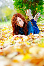 Beautiful woman is lying on leaves in park Stock Photography