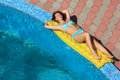 Beautiful woman lying on an mattress near pool Stock Photography