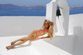 Beautiful woman lying on a pool of the view of the sea in a sexy swimsuit color in santorini Royalty Free Stock Photo