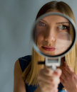 Beautiful woman with magnifying glass in hands looks in a camera lens Stock Image