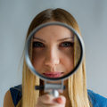 Beautiful woman with magnifying glass in hands looks in a camera lens Royalty Free Stock Photos