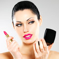 Beautiful woman makes makeup applying pink lipstick lips Royalty Free Stock Photos