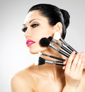 Beautiful woman makeup brushes near her face pretty girl poses studio cosmetic tools Royalty Free Stock Photography