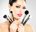 Beautiful woman makeup brushes near her face pretty girl poses studio cosmetic tools Royalty Free Stock Images