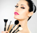 Beautiful woman with makeup brushes near her face pretty girl poses at studio cosmetic tools Stock Images