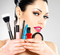 Beautiful woman with makeup brushes near her face pretty girl poses at studio cosmetic tools Royalty Free Stock Photos