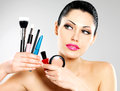 Beautiful woman with makeup brushes near her face pretty girl poses at studio cosmetic tools Stock Photos