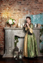 Beautiful woman in medieval dress near fireplace young long Stock Photography
