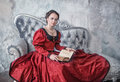 Beautiful woman in medieval dress on the sofa with book Royalty Free Stock Photo