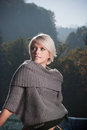 Beautiful woman in misty mountains young blond a stylish cowl neck sweater standing against a backdrop of forested mountain peaks Royalty Free Stock Photos