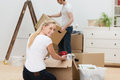 Beautiful woman moving house women kneeling on the floor alongside a cardboard box and turning to smile at the camera as her Stock Photography