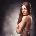 Beautiful woman with naked back portrait in the fog over dark background Stock Photos
