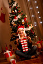 Beautiful woman near Christmas tree opening gifts Stock Photos