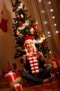 Beautiful woman near Christmas tree opening gifts Royalty Free Stock Photo