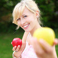 Beautiful woman offering an apple smiling young a yellow to the viewer while holding a delicious ripe red one in her other hand Royalty Free Stock Images