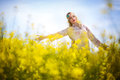 Beautiful woman in oilseed rape flowers Royalty Free Stock Photo