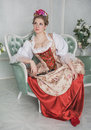 Beautiful woman in old-fashioned medieval dress on the sofa Royalty Free Stock Photo