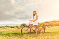 Beautiful woman with an old red bike in a wheat field Royalty Free Stock Photo