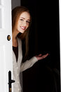 Beautiful woman is opening door and inviting to come in smiling Royalty Free Stock Photography