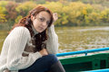 Beautiful woman out boating young sitting in a rowboat on a lake or river in autumn looking pensively at the camera close up Stock Image