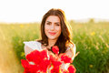 Beautiful woman over Sky and Sunset holding a poppies bouquet and smiling Royalty Free Stock Photo